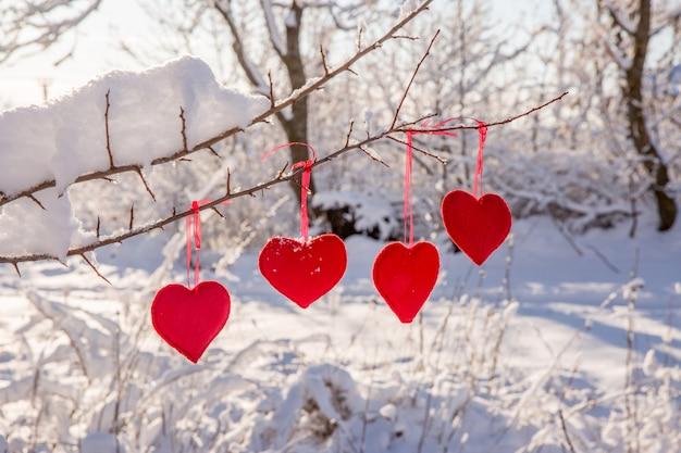 Girlanda czerwonych serc wisi na zaśnieżonej gałęzi