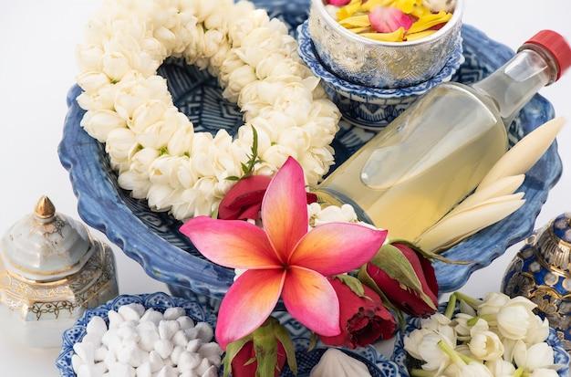 Girlanda jaśminowa i kolorowy kwiat w miseczkach na wodę dekorująca i pachnąca woda, perfumy, wapień marglisty, pistolet fajkowy izolowany na festiwal songkran lub tajski nowy rok.