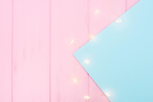 Girlanda lampek choinkowych na niebieskim papierze granicy na różowym drewnianym