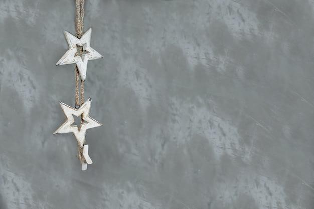 Girlanda, wisiorek z drewnianych gwiazd na jasnym tle z nicią lnianą. małe drewniane gwiazdy na szarym tle.