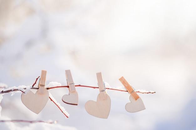 Girlanda z drewnianych serc wisi na zaśnieżonej gałęzi
