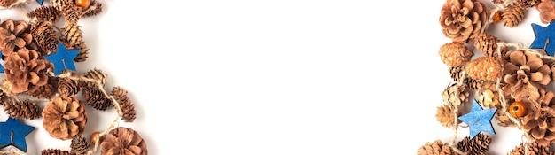Girlanda z szyszek i drewnianych figurek niebieskich gwiazd. naturalne materiały, ekologiczne dekoracje na nowy rok. szeroki baner z białym tłem