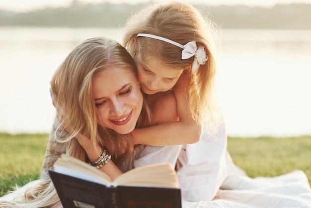 Girly próbuje szybko czytać. mama i córka czytając książkę w słoneczny dzień na trawie z jeziorem w tle.