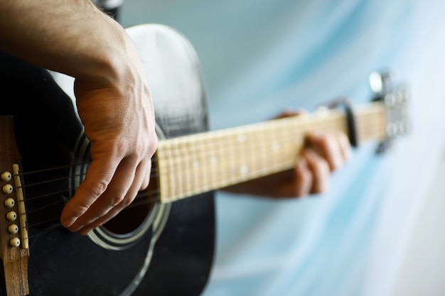 Gitara akustyczna dla artysty grającego na strunowym instrumencie muzycznym na scenie. czarna gitara z kapo. tło muzyczne.