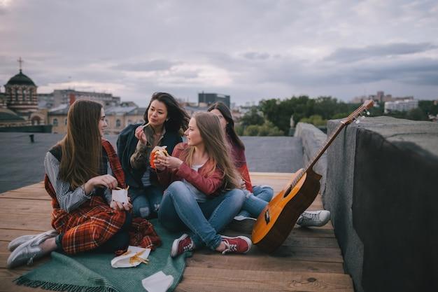Gitara akustyczna i spotkania z przyjaciółmi na dachu. uśmiechnięte dziewczyny z fast foodami, niezwykłe miejsca do odpoczynku i komunikacji, wspólne spędzanie czasu, koncepcja wesołej i radosnej atmosfery