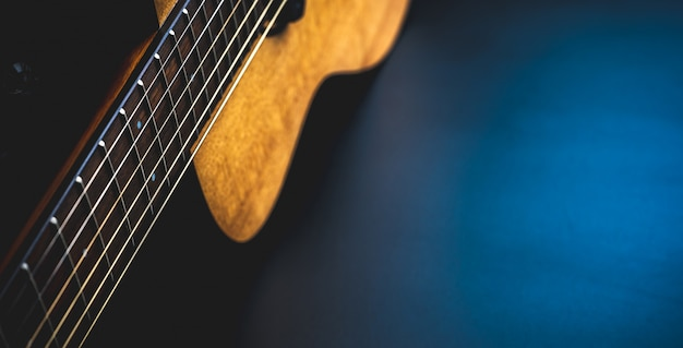 Gitara akustyczna, instrument muzyczny oparty o ciemną czarną ścianę z miejsca kopiowania, szczelnie-do góry drewniana gitara klasyczna