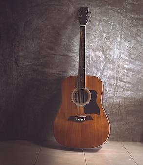 Gitara akustyczna na ciemnej ścianie w tonie vintage