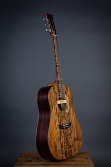 Gitara akustyczna na krześle w czarnej ścianie.