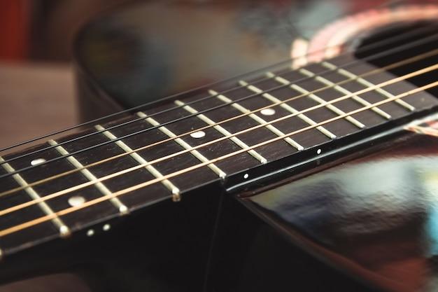 Gitara akustyczna podstrunnica z ciemnego drewna na ciemnej drewnianej powierzchni. pojęcie muzycznego hobby, dziecięcej szkoły artystycznej.
