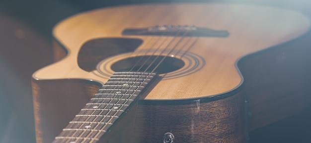 Gitara akustyczna z pięknym drewnem na czarnym tle z pięknym światłem.