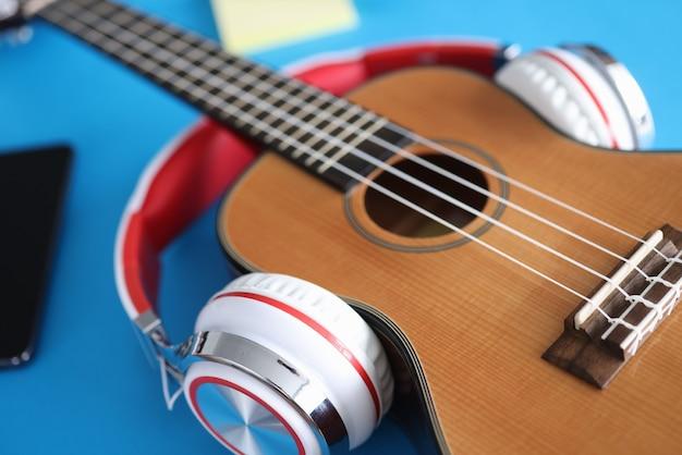 Gitara akustyczna ze słuchawkami leży na stole