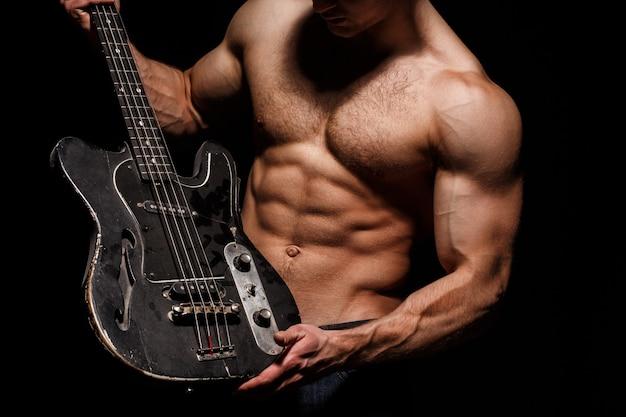 Gitara. człowiek tułowia. grać na gitarze. mięśnie klatki piersiowej, sześciopak, brzuch, triceps. festiwal muzyczny. instrument na scenie i zespole. silny, muskularny, umięśniony mężczyzna, kulturystyka. koncepcja muzyki. gitara elektryczna.