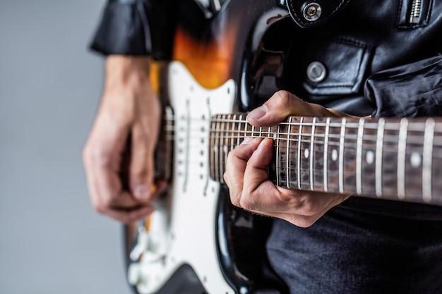 Gitara elektryczna. powtórzenie zespołu rockowego. festiwal muzyczny. mężczyzna gra na gitarze. bliska ręka gra na gitarze.