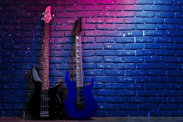 Gitara elektryczna w świetle neonów na tle ciemnej ściany z cegły