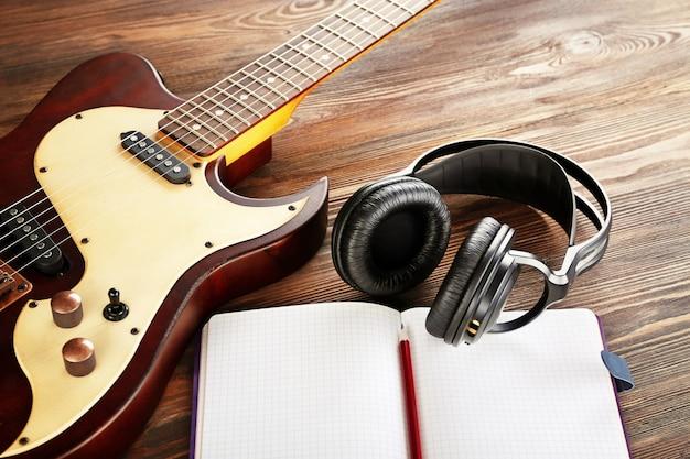 Gitara elektryczna ze słuchawkami i notatnikiem na drewnianym stole z bliska