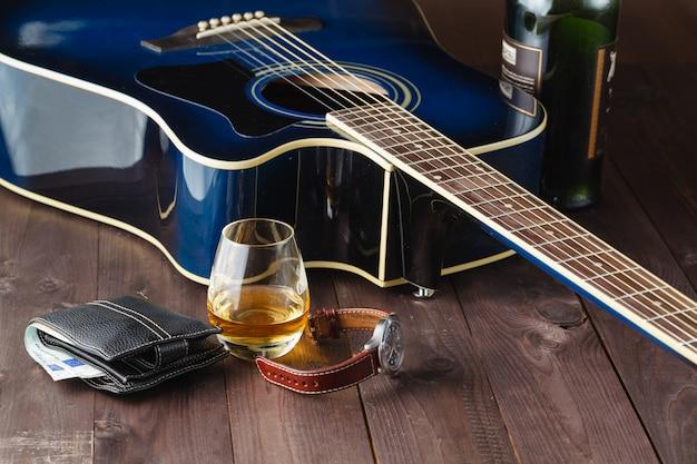 Gitara i whisky na drewnianym stole