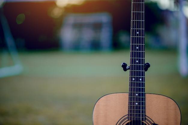 Gitara jest umieszczona na zielonym trawniku. muzyczna koncepcja i jest kopia przestrzeń.