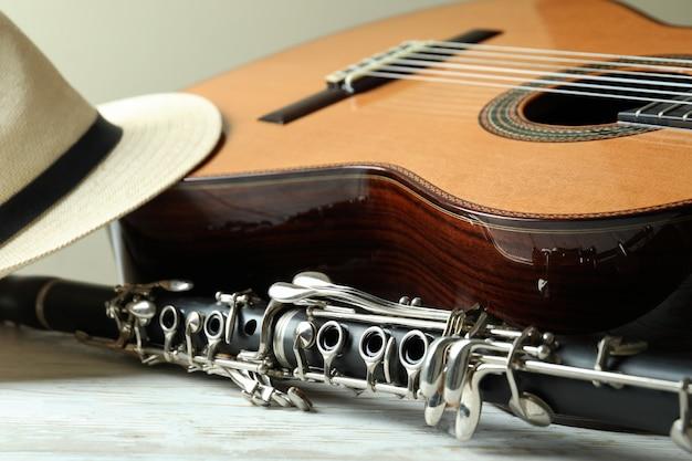 Gitara klasyczna, klarnet i kapelusz na białym drewnianym stole
