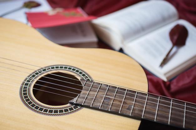 Gitara leżąca na czerwonym materiale, suszone kwiaty, książki na czerwonym tle, rozproszone książki, wieczne pióro, artystyczna atmosfera