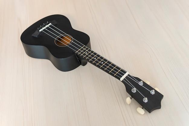 Gitara na teksturowanym drewnie. gitara akustyczna na drewnianym stole z miejscem na tekst. instrument muzyki ludowej. klasyczny czarny koncert ukulele