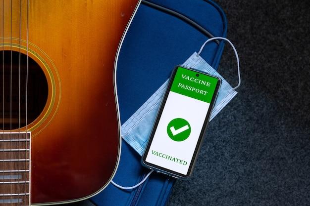Gitara, podróżna torebka bagażowa, maska ochronna na twarz i cyfrowy paszport szczepionkowy w telefonie komórkowym. nowa normalna koncepcja podróży