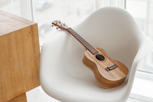 Gitara ukulele na białym stołku, nauka gry na gitarze, kopia przestrzeń