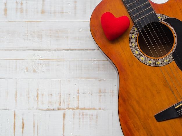 Gitary i czerwieni serce na białym drewnianym tekstury tle