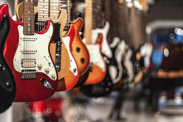 Gitary, prezentacja z wiszącymi w rzędzie gitarami