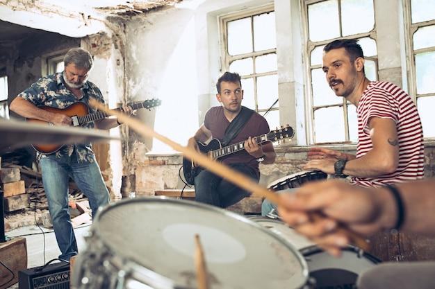 Gitarzyści elektryczne i perkusista za zestawem perkusyjnym.