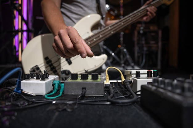Gitarzysta basowy na scenie z zestawem efektów przesterowanych.