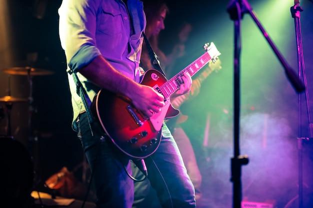 Gitarzysta bawić się gitarę elektryczną na rockowym koncercie