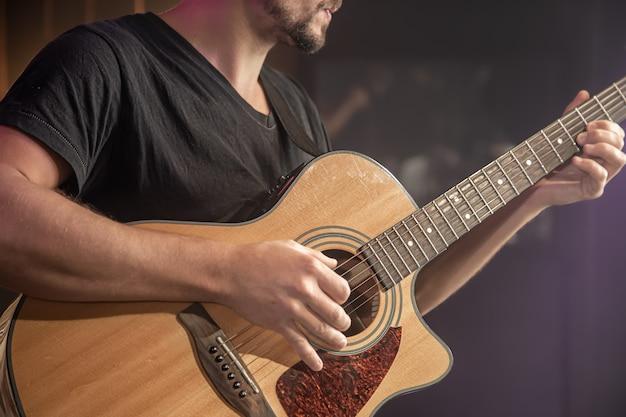 Gitarzysta gra na gitarze akustycznej na czarnej przestrzeni niewyraźne z bliska.