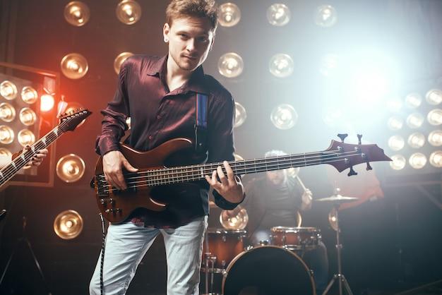 Gitarzysta gra na gitarze basowej, zespole rockowym