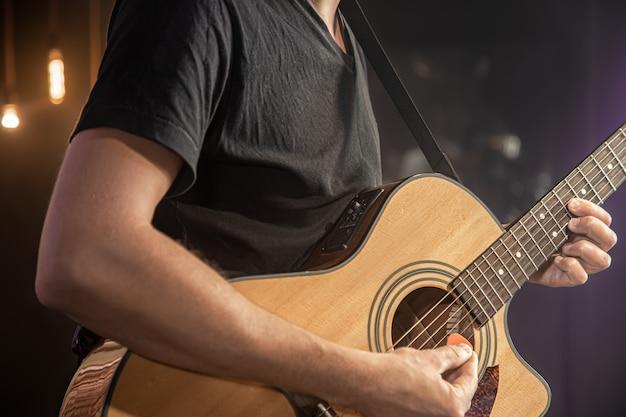 Gitarzysta gra na koncercie na gitarze akustycznej