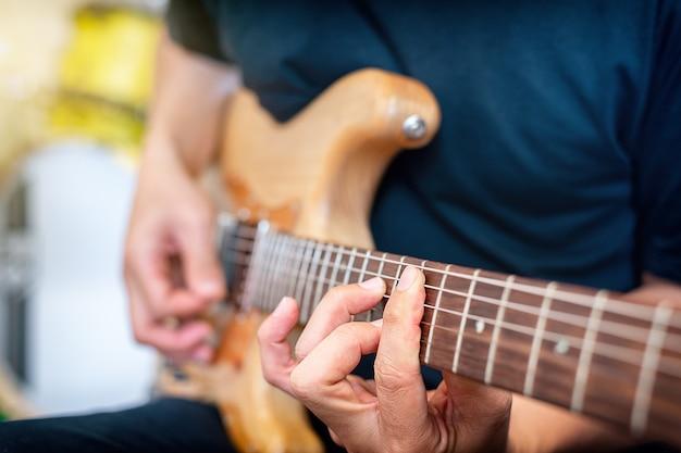Gitarzysta gra powtórzenie zespołu muzyki rockowej. przycięty obraz elektryczny.