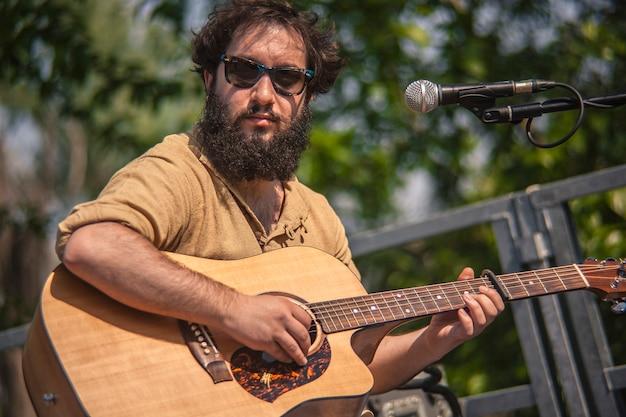 Gitarzysta gra siedząc na koncercie rockowym na żywo