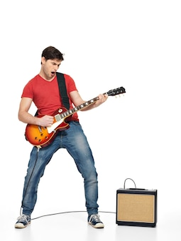 Gitarzysta mężczyzna gra na gitarze elektrycznej z jasnymi emocjami, na białym tle na białej ścianie