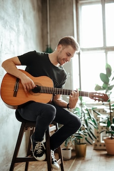 Gitarzysta mężczyzna gra na gitarze w domu