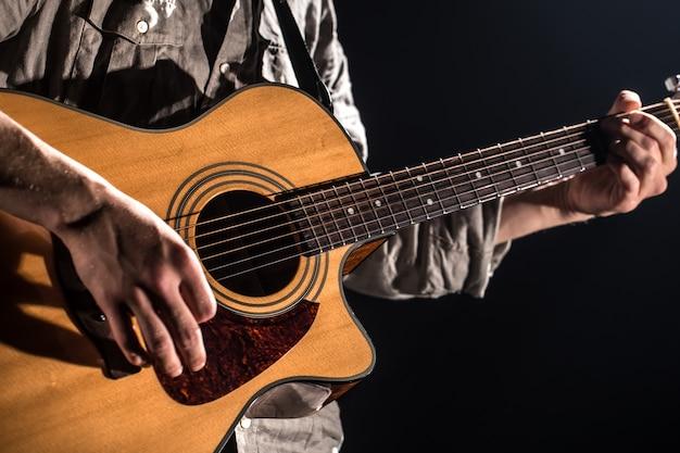 Gitarzysta, muzyka. młody człowiek gra na gitarze akustycznej na czarnej ścianie na białym tle