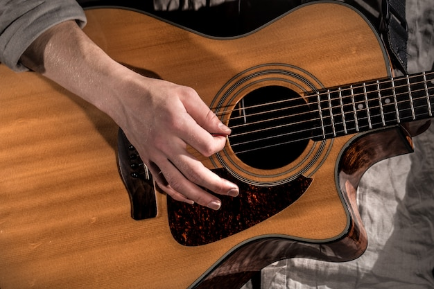 Gitarzysta, muzyka. młody człowiek gra na gitarze akustycznej na czarno na białym tle