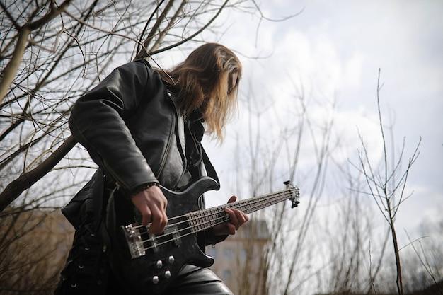 Gitarzysta rockowy na schodach. muzyk z gitarą basową w skórzanym garniturze. metalista z gitarą na tle industrialnego kroku.
