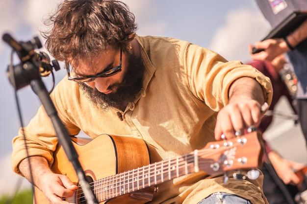 Gitarzysta stroi gitarę na scenie, na której wkrótce wystąpi na koncercie