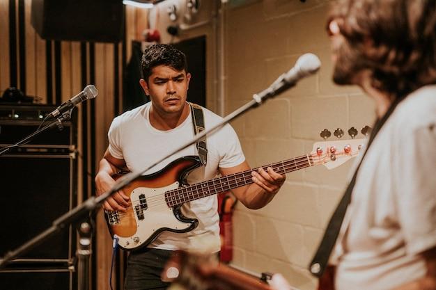 Gitarzysta zespołu muzycznego wykonujący powtórkę w studiu nagraniowym