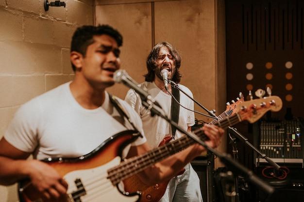 Gitarzysta zespołu rockowego wykonujący powtórkę w studiu nagraniowym