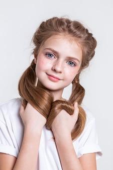 Gładka biała koszulka. atrakcyjna mała dziewczynka z jasnymi piegami i dużymi niebieskimi oczami przewracającymi jej mocne włosy
