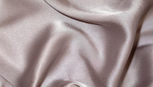 Gładka elegancka beżowa jedwabna tekstura tło
