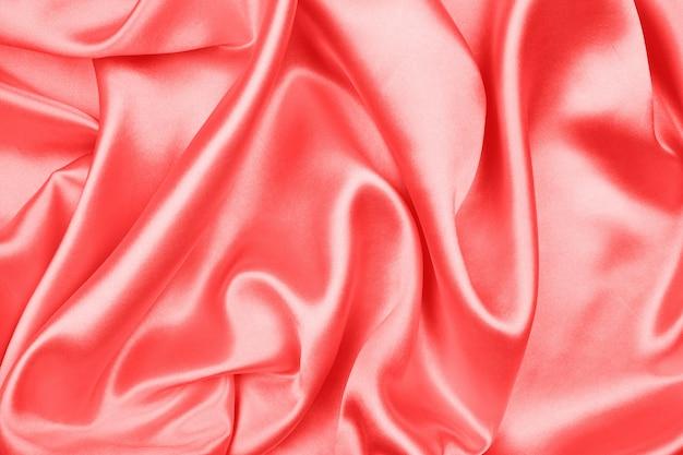 Gładka elegancka czerwona jedwabna lub satynowa tekstura może służyć jako abstrakcyjne tło, tkanina