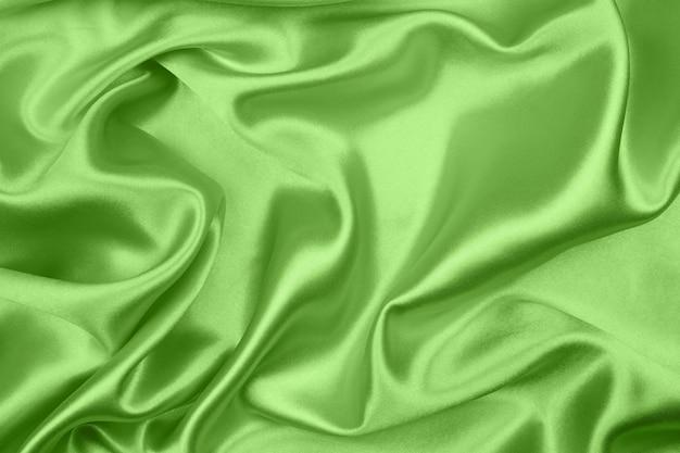 Gładka, elegancka zielona jedwabna lub satynowa faktura może służyć jako abstrakcyjne tło, tkanina