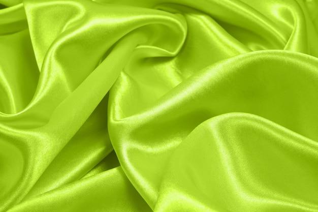 Gładka elegancka zielona tekstura jedwabiu lub satyny może służyć jako abstrakcyjne tło, wzór tkaniny