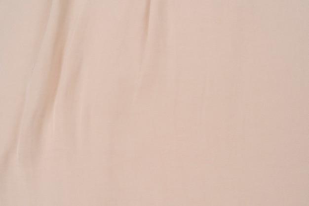Gładka, elegancka złota jedwabna lub satynowa luksusowa tekstura tkaniny może służyć jako beżowy jedwab w tle ślubu